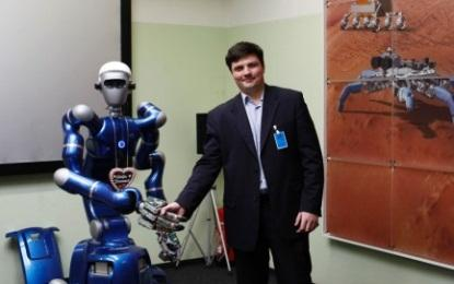Associate Professor Vladimir Mulukha, PhD, Telematics Department of St. Petersburg Polytechnic University, shakes hands with the mobile humanoid 'Justin,' one type of robot utilized in Ford's space robots research project to advance connected-vehicle communications. (Photo: Ford Motor Co.)