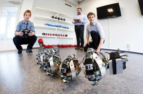 SINTEF researchers Pal Liljeback and Aksel Transeth, along with Knut Robert Fossum of NTNU's CIRiS, play with Wheeko the snake robot.(Source: SINTEF/Thor Nielsen)