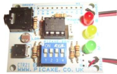 The AXE092 PICAXE Kit. The big black thing at the upper left is the programming socket. The small black thing at the lower left is a push switch. The DIP switch is for disconnecting outputs to use them for other things. The upper wires on the right-hand side go to the battery; wires on the lower right-hand side go to a piezo sounder.