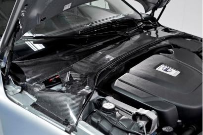 This shows an installed plenum cover created from the carbon fiber energy storage material developed by Volvo. It replaces three items in a standard car -- the rally bar, traditional plenum cover and the start-stop battery -- and saves more than 50 percent of system weight. (See full size image.)(Source: Volvo Car Group)