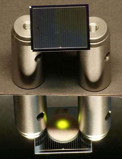This two-sided (bi-facial) silicon solar cell -- positioned on aluminum cylinders -- is illuminated from above by an infrared laser.(Source: Fraunhofer ISE)