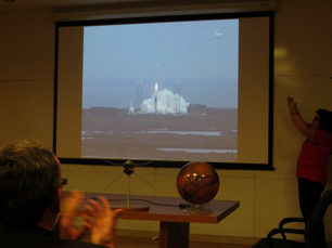 Fran Bagenal raising her hands in trump as the audience in the LASP auditorium watched the live broadcast of the MAVEN launch. A model of the satellite rests on the table next to the globe of Mars. (Source: Eric Bogatin)