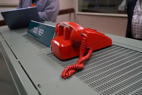 The red phone sitting on the Department of Defense desk.
