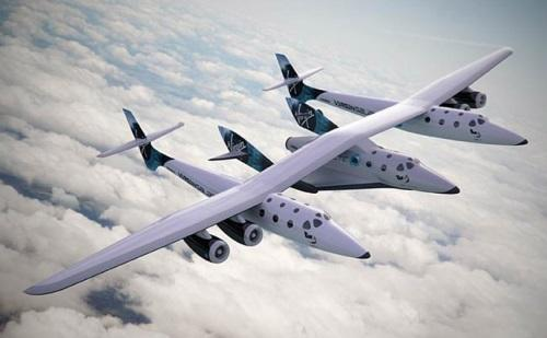 SpaceShip Two is carried to 50,000 feet on what looks like two planes fused together.