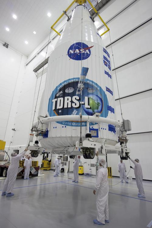 Inside the Astrotech payload processing facility in Titusville, Fla., NASA's Tracking and Data Relay Satellite (TDRS-L) spacecraft has been encapsulated in its payload fairing. It is being lifted by crane for mounting on a transporter for its trip to Launch Complex 41 at Cape Canaveral Air Force Station. The TDRS-L satellite will be a part of the second of three next-generation spacecraft designed to ensure vital operational continuity for the NASA Space Network. TDRS-L is scheduled to launch from Cape Canaveral's Space Launch Complex 41 atop a United Launch Alliance Atlas V rocket at 9:05 p.m. EST on Jan. 23, 2014, the start of a 30-minute launch window. The current Tracking and Data Relay Satellite system consists of eight in-orbit satellites distributed to provide near continuous information relay contact with orbiting spacecraft ranging from the International Space Station and Hubble Space Telescope to the array of scientific observatories. Click here for a larger image. (Source: NASA/Kim Shiflett)