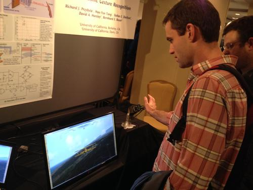 Chirp sensor: An ISSCC attendee demonstrates the ultrasonic gesture recognition sensor on a flight game.(Source: EE Times/Jessica Lipsky)