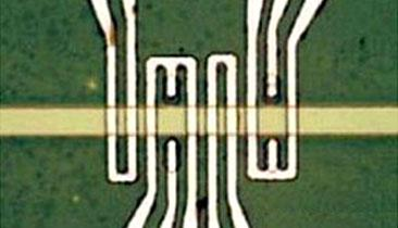 A picture of spin wave devices showing magneto-electric cells used for voltage-controlled spin wave generation in the spin wave bus material (yellow stripe). The yellow stripe is about four micrometers in diameter.(Source: UCLA Henry Samueli School of Engineering and Applied Science)