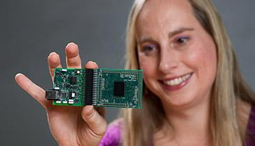 Professor Hasler holds an FPAA board she is using to emulate biologically based neural networks. (Source: Rob Felt courtesy of Georgia Tech)