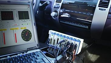 Test hardware can operate in a vehicle by measuring data from sensors and communicating with automotive electronic systems.