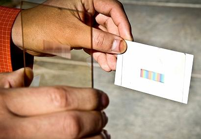A thin rectangular plastic or glass layer -- or 'polychromat' -- developed by engineers at the University of Utah sorts sunlight into colors that can be absorbed by solar cells to increase their efficiency without increasing the cost. (Source: Dan Hixson, University of Utah)