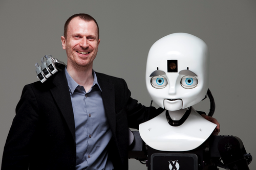 Robotics professor Matthias Scheutz poses for a portrait with his team's robot, Cindy, in the Human Robot Interaction Lab. (Source: Kelvin Ma/Tufts University)