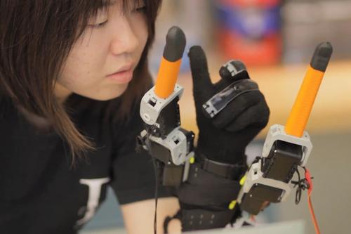 MIT doctoral candidate Faye Wu shows that by following the motions of the fingers the two robotic fingers adjacent to thumb and pinky can help users perform tasks with one hand that would ordinarily take two. (Source: MIT)