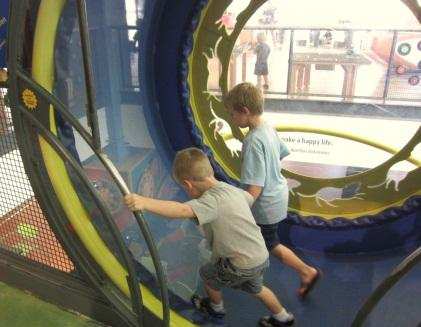 Kids step inside a gerbil wheel at Madison Children's Museum. By continuing to walk, they find out they are actually generating energy, as small LED lights in front of them start to light up. (Source: Junko Yoshida)