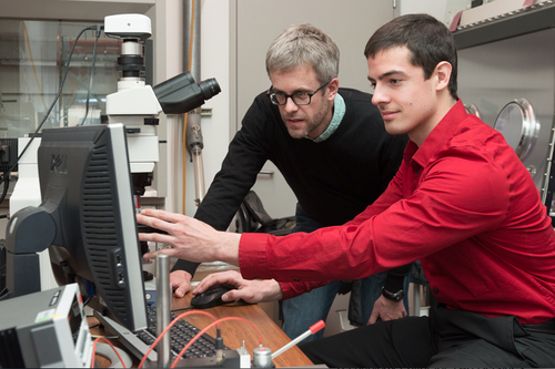 Professor Mike McGehee and doctoral candidate Colin Bailie at Stanford University use a microscope to examine a perovskite solar cell.