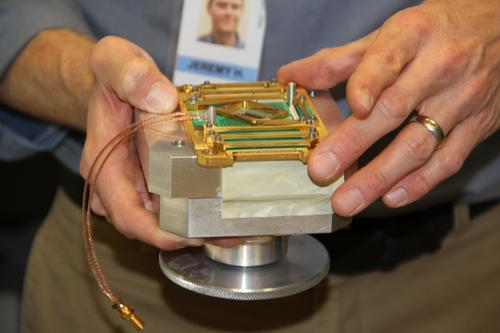 Jeremy Hilton, vice president of processor development of D-Wave, holding the 'Vesuvius' 512-qubit module that will be supercooled down to .2 milliKelvin using a 10kWatt refrigerator.