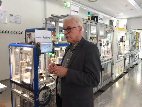 Detlef Zuehlke, director of innovation factory systems at the German Research Center for AI (DFKI) show how the smart factory of the future will use hot-interchangeable modules (background) that can be arranged in any order.