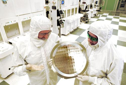 Professor Michael Liehr (left) of SUNY Polytechnic Institute's Colleges of Nanoscale Science and Engineering (SUNY Poly CNSE) and Bala Haran (right) of IBM Research inspect 7-nanometer wafer of test chips developed in alliance partnership between IBM and SUNY Poly CNSE.