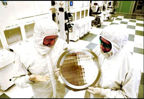 Michael Liehr of the SUNY College of Nanoscale Science and Engineering, left, and Bala Haranand of IBM examine a wafer comprised of the new SiGe 7nm-based integrated circuits.  (Source/Credit: Darryl Bautista/IBM)