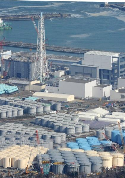 An aerial photo shows the No.3 (L) and No. 4 reactors of the Fukushima No. 1 nuclear power plant being decommissioned and tanks containing radioactive contaminated water in Fukushima on Feb. 21, 2015. (Photo credit: The Yomiuri Shimbun via AP Images)