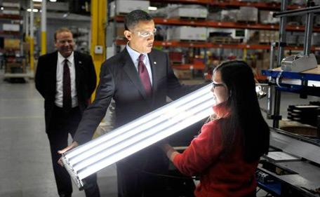 President Obama inspects some new materials used to make more energy efficient fluorescent-like tubular light bulbs for his Materials Genome Initiative (MGI).