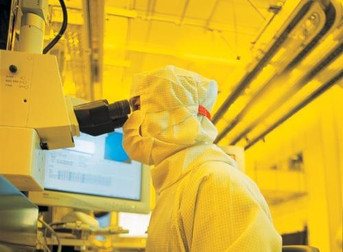 A fab worker inspects a 12-inch wafer. (All images: TSMC)