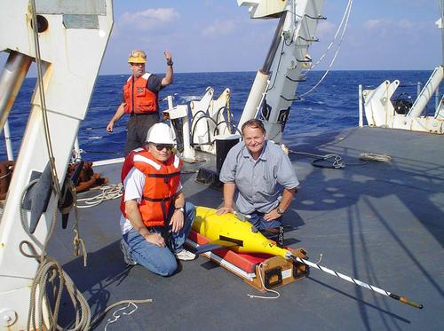 On-deck short-fin Seaglider version shows antenna windings on tail and its comparative size to crew members. (Source: University of Washington)
