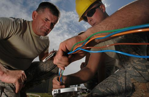 US Air Force technicians splice fiber optic cable. (Source: Kenny Holston, Flickr)