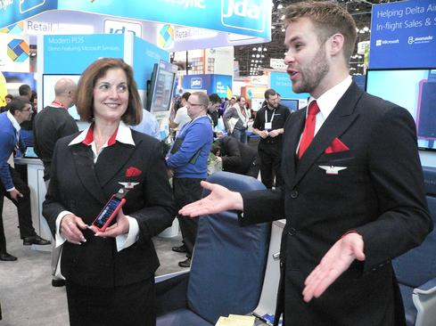 Delta flight attendants demonstrate Dynamics Retail Point-Of-Sale capabilities supported on Windows Phones.