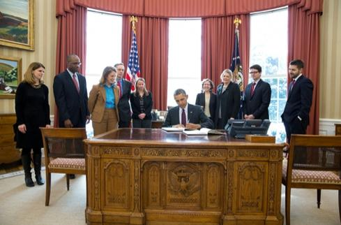 President Obama, surrounded by budget staff, signs $3.9 trillion budget for fiscal year 2015 sent to Congress March 4, 2014.