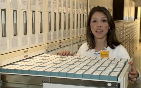 A graduate student reviews microfilm records at the National Archives and Records Administration (from NARA video).