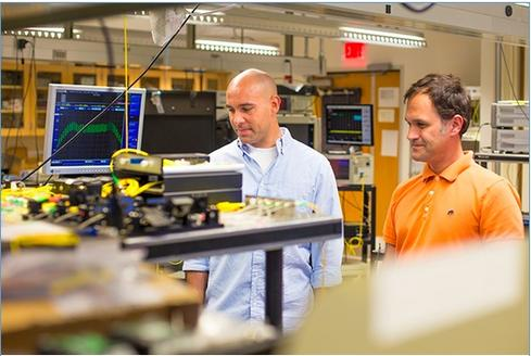 Eduardo Temprana, left, and Nikola Alic at work in the Photonic Systems lab.