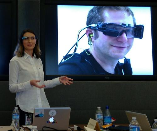 Sarah Price from Google X, wearing the current model of Google Glass, shows a photo of Thad Starner with the first prototype.  (Source: jurvetson/Flickr)