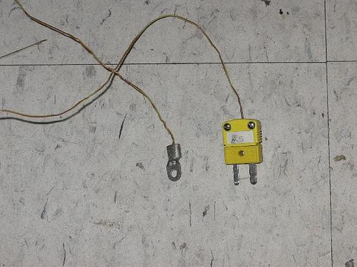 A thermocouple junction encapsulated by a mounting tab. The yellow connector indicates a K type thermocouple and will fit into any thermocouple thermometer. The connector will be black for a J type, blue for a T type, purple for an E type, and so on.