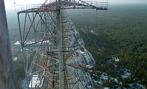 Shown here is the Duga-1 RADAR array within the Chernobyl Exclusion Zone. On the right side can be seen an array of pairs of cylindrical/conical cages; these are the driven elements, fed at the facing points with a form of ladder line suspended from stand-off platforms at the top right of the image. A backplane axel reflector of small wires is seen left of center, most clearly at the bottom of the image. (By Necator - the English language Wikipedia (log), Public Domain)