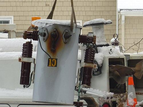 A leaking power transformer was removed from a pole, to be carried away.