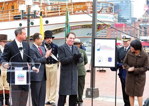 In November 2011, Maryland officials, including Gov. Martin O'Malley and Baltimore Mayor Stephanie Rawlings-Blake (flanking logo), unveiled the logo for the Star-Spangled Sailabration, which took place June 2012. The city deployed the PSIM system from VidSys during this event.