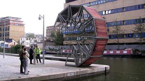 Heatherwick Studio designed this bridge to span an inlet of the Grand Union Canal, and it was completed in 2004. The bridge uses hydraulics to curl up to let boats through and uncurl to let pedestrians cross.