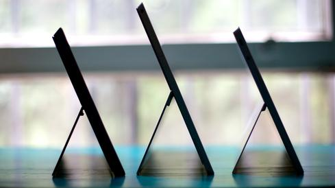 The Surface Pro 3, center, offers more power than the Surface Pro, left, is almost as thin as the Surface 2, right, and boasts a better screen than either.