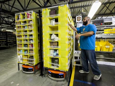 Amazon employee picks items from a Kiva robot in its Seattle distribution center. (Source: Amazon, via Business Wire)