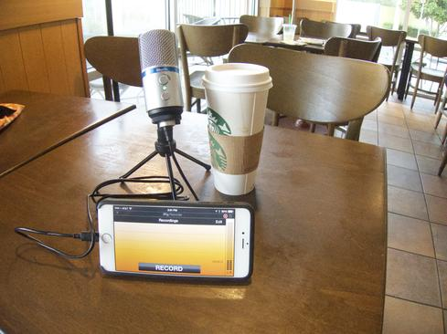 The iRig Mic Studio on a table next to an iPhone 6+. The coffee cup, for relative size, is a 'venti.'