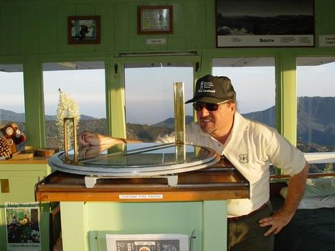 USFS volunteer fire lookout Charles White at the Osborne Fire Finder at Vetter Mountain Lookout in the Angeles National Forest. The Osborne Fire Finder is a device made in the 1920s and still in use today.  (Image: Charles White via Wikipedia)
